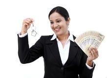 拿着房子钥匙和货币笔记的女实业家 免版税库存照片