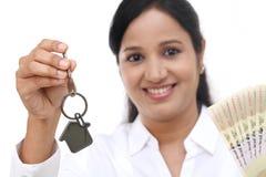 拿着房子钥匙和货币笔记的女实业家 图库摄影