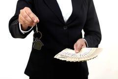 拿着房子钥匙和货币笔记的女实业家 库存照片