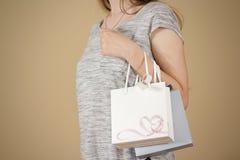 拿着手中与心脏的女孩空白两纸礼物袋子嘲笑u 免版税库存图片