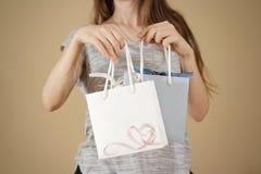 拿着手中与心脏的女孩空白两纸礼物袋子嘲笑u 免版税库存照片