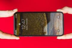 拿着手中新的苹果计算机Iphone x旗舰智能手机 免版税库存图片