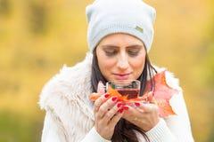 拿着手中热的红色茶的年轻可爱的妇女 放松在秋天自然用热的茶 免版税图库摄影