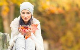 拿着手中热的红色茶的年轻可爱的妇女 放松在秋天自然用热的茶 库存照片