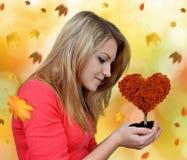 拿着手中秋季树的女孩 库存照片