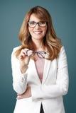 拿着手中eyewear的微笑的妇女 免版税库存照片