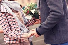 拿着手和花的夫妇的中央部位 免版税库存图片