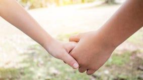 拿着手夫妇的亚裔小女孩一起显示Relationsh 免版税库存照片