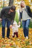 拿着手女孩的愉快的父母去在秋天公园 免版税库存照片
