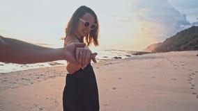 拿着手妇女主导的男朋友的年轻夫妇走往在空的海滩的日落 海愉快的暑假 股票录像