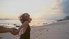 拿着手妇女主导的男朋友的年轻夫妇走往在空的海滩POV旅行概念的日落 影视素材