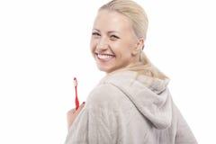 拿着手工牙刷的愉快的笑的白种人白肤金发的女孩 免版税图库摄影
