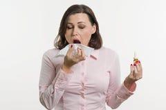 拿着手帕和鼻孔喷射的病的女实业家 奶油被装载的饼干 图库摄影