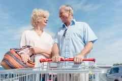 拿着手推车的老人,当看他的充满爱时的妻子 免版税图库摄影