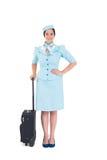 拿着手提箱的俏丽的空中小姐 免版税库存照片