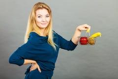 拿着手提篮用里面果子的妇女 免版税库存图片