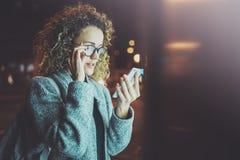 拿着手智能手机的眼睛玻璃的妇女在夜大气城市 使用手机的女性手 特写镜头 免版税图库摄影