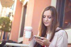 拿着手机和咖啡的年轻可爱的妇女 免版税库存图片