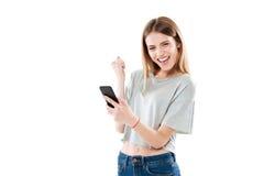 拿着手机和庆祝胜利的愉快的快乐的女孩 免版税库存照片
