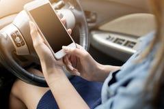 拿着手机和把手指放的女性的手在汽车里面的屏幕上 免版税库存图片