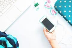 拿着手机和白色膝上型计算机有绿色文具和女孩辅助部件的平的位置妇女手 免版税库存图片