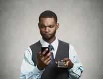 拿着手机和计算器的企业经营者 免版税库存照片