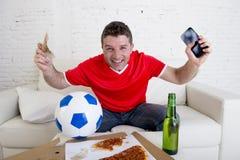 拿着手机和金钱在他的手上的年轻人观看fottball比赛在电视互联网赌博的概念 免版税库存图片