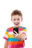 拿着手机或智能手机的微笑的男孩采取自已 库存照片