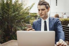 拿着手机手中和坐在膝上型计算机旁边的商人 正面图 免版税库存图片