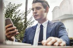 拿着手机手中和看屏幕的年轻商人 免版税库存图片