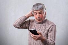 拿着手机的一个震惊成熟人接触他的头用手 有灰色头发的一个年长人吃惊,当l时 库存照片