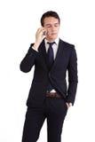 拿着手机的不快乐的年轻白种人商人 库存照片