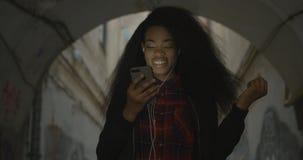 拿着手机的可爱的愉快的非洲女孩的画象 她跳舞,当听到音乐通过时 影视素材