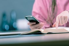 拿着手机的妇女,当阅读书时 库存照片