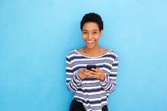 拿着手机的微笑的年轻黑人妇女由蓝色背景 免版税库存图片