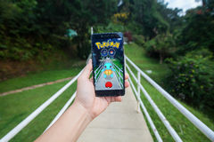 拿着手机的手演奏Pokemon是 免版税图库摄影