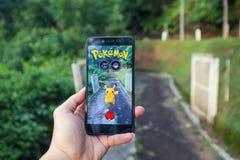 拿着手机的手演奏Pokemon是 免版税库存照片