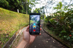 拿着手机的手演奏Pokemon是 图库摄影