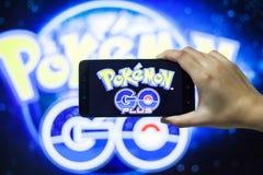 拿着手机的手演奏Pokemon去比赛有迷离背景 免版税库存照片