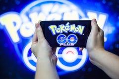 拿着手机的手演奏Pokemon去比赛有迷离背景 库存照片