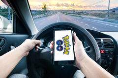 拿着手机的手演奏Pokemon去比赛,当驾驶时 免版税库存照片