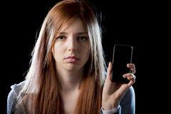 拿着手机的担心的少年,胁迫被偷偷靠近的受害者的互联网网络滥用了 免版税库存照片