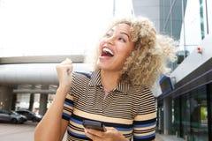 拿着手机的笑的妇女 免版税库存照片