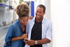 拿着手机的美好的夫妇笑和站立 免版税库存照片
