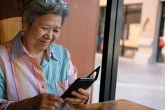拿着手机的老妇人在庭院里 年长女性texti 库存图片