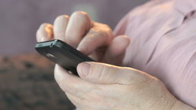 拿着手机的老起皱纹的手 关闭 股票视频