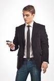 拿着手机的年轻愉快的人 免版税库存照片