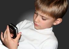 拿着手机的年轻男孩 免版税库存图片