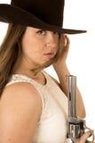 拿着手枪的坚韧女牛仔凝视在照相机的表示下 免版税库存照片