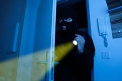 拿着手电的窃贼,当加入房子时 免版税库存图片